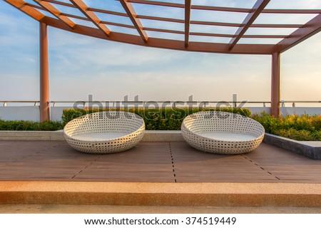 Relax corner on condominium rooftop garden with chairs. - stock photo