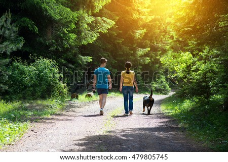 Relax family walk with dog in the wood.Colored and under exposed photo