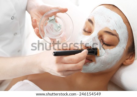 Relax in the beauty parlor, cucumber mask. Cosmetic procedure woman's face in the mask mitigating and cucumber slices on eyes  - stock photo