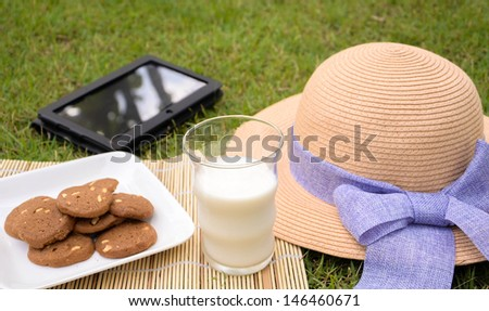 Relax in the garden with cookie, milk and tablet - stock photo