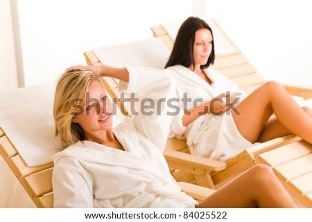 Relax luxury spa beauty women enjoy refreshments lying on sun-beds - stock photo