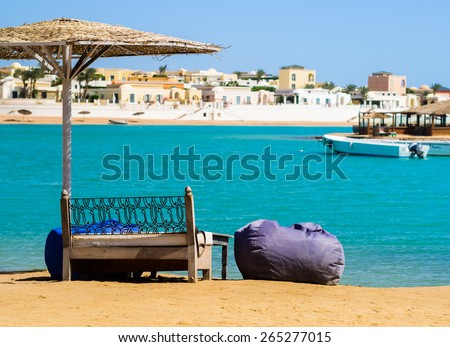 Relax on the beach. Coastal landscape with beach umbrella, sea and resort view. Tropical beach on the island. Summer landscape - beach scene for your concept of sea vacation. - stock photo