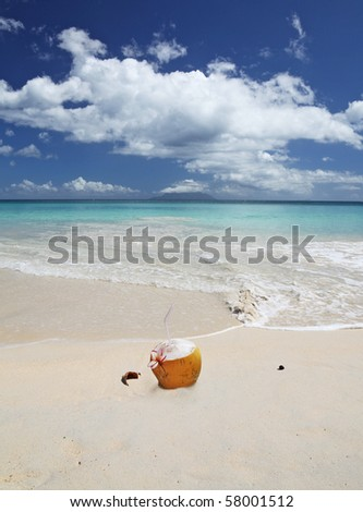 Relax Seychelles Style, Coconut with Straw and National flower on the stunning Indian Ocean beach with Silhouette island in the background - stock photo