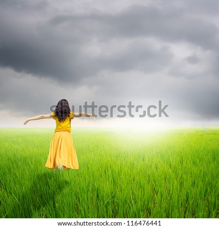 Relax Woman in green rice fields with rainclouds