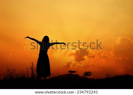 Relax woman standing and sunset silhouette - stock photo