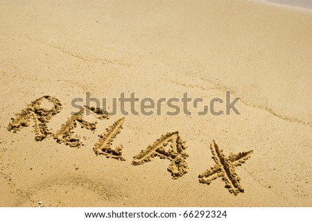 Relax word on a sandy beach - stock photo