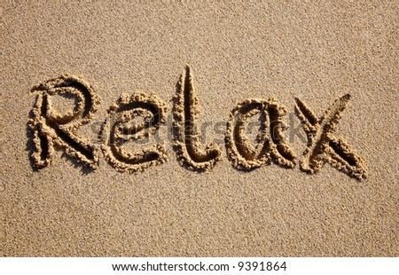 Relax, written on a sandy beach. - stock photo
