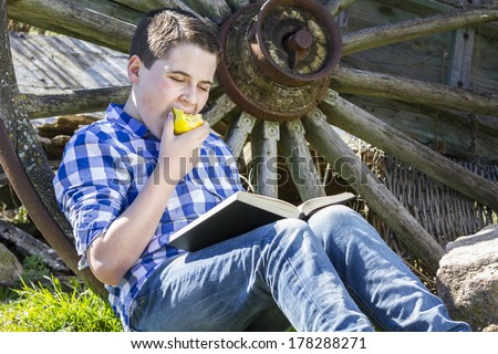Relax.Young boy reading a book in the woods eating an apple