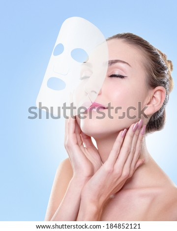 Relax Young woman with cloth facial mask isolated on blue background, concept for skin care and sunburn protection, caucasian - stock photo