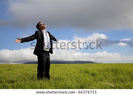Relaxation businessman standing on the meadow - stock photo
