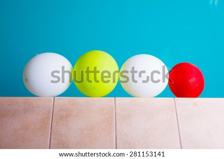 Relaxation carefree resort concept. Colorful balloons at hotel swimming pool - stock photo