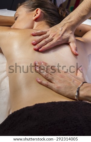 Relaxation. Masseur doing massage on woman body in the spa salon. Beauty treatment concept. - stock photo