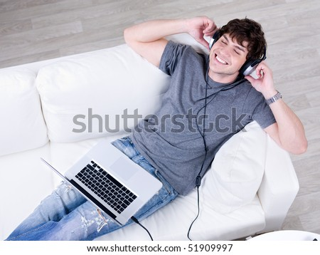 Relaxation of young happy man lying on the sofa with laptop and listening music in headphone - stock photo