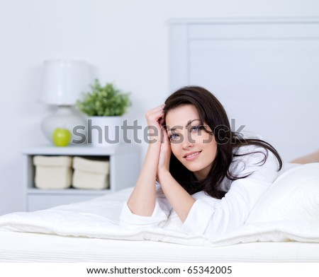 Relaxation on a bed of young beautiful brunette woman  -  indoors - stock photo