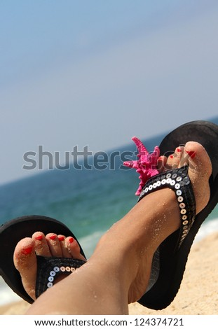 Relaxation on the beach - female feet decorated with sea star - stock photo
