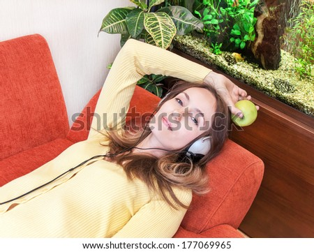 Relaxation, resting. Caucasian girl is listening music. She is on red sofa with headphones and apple, near aquarium and green plant. Close up portrait. Indoor.  - stock photo