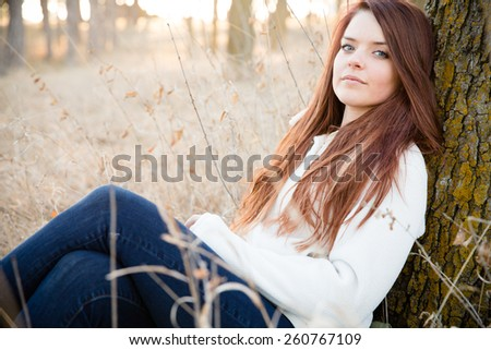 Relaxation - This is a shot of a beautiful young woman sitting in some tall grass next to a tree enjoying the nice weather. Shot with a shallow depth of field. - stock photo