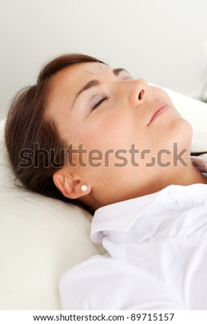 Relaxed acupuncture patient with eyes closed, undergoing a facial beauty treatment - stock photo