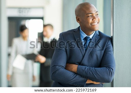 relaxed african american businessman looking out the window