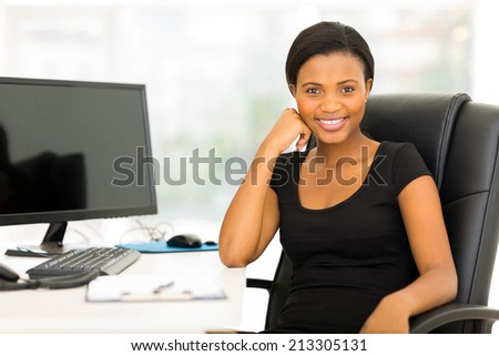 relaxed african businesswoman sitting in modern office - stock photo