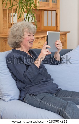 Relaxed and happy aged woman sitting with tablet pc on her sofa