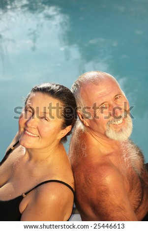 Relaxed and happy retired couple sitting by the water