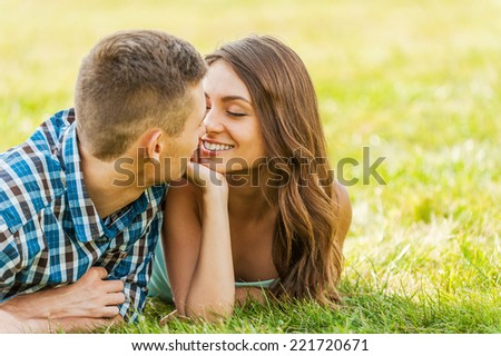 Relaxed and in love. Young couple lying on the grass and enjoying each other - stock photo