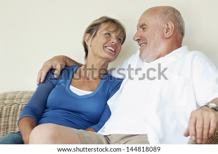 Relaxed and loving middle aged couple sitting on wicker couch - stock photo