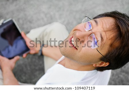 Relaxed and positive man is surfing on his tablet - stock photo