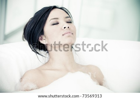 Relaxed asian woman resting in her bathtub - stock photo