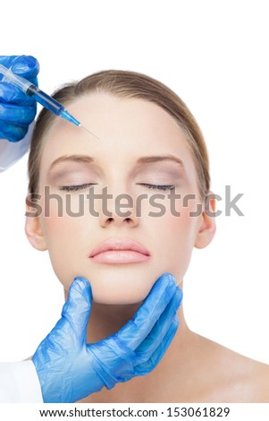 Relaxed attractive model on white background having botox injection on the forehead - stock photo