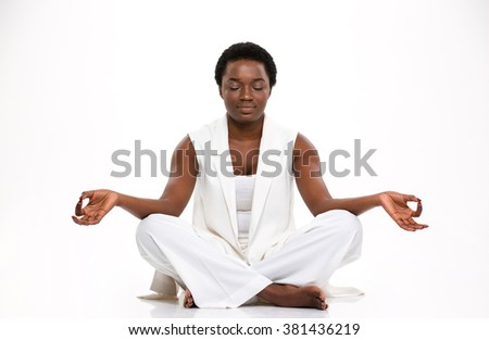 Relaxed beautiful african american young woman sitting and  meditating in yoga pose over white background - stock photo