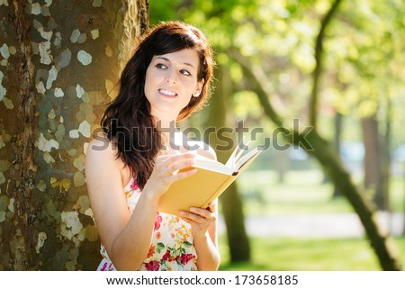 Relaxed beautiful woman reading book in park on summer or spring. - stock photo
