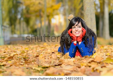 Relaxed beautiful woman thinking and lying down in autumn park. Happiness and relaxing over fall golden leaves. - stock photo