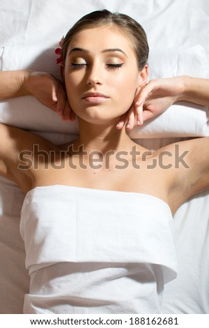 relaxed beautiful young woman lying on her back and getting beauty massage enjoying treatment picture  - stock photo