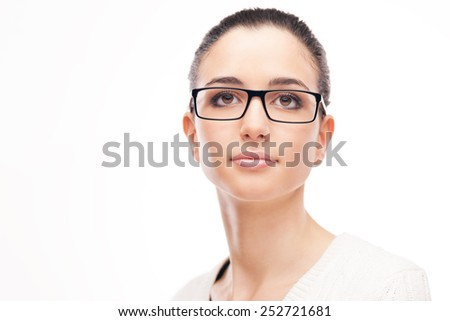 Relaxed beautiful young woman posing on white background wearing black glasses - stock photo