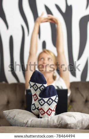 Relaxed, beautiful young woman sitting on sofa, using laptop - stock photo