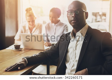 Relaxed black business man at office, people in background - stock photo