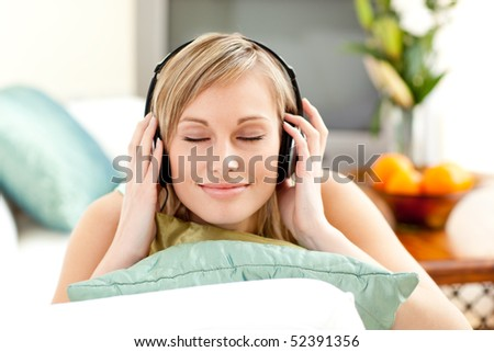 Relaxed blond woman listening music lying on a sofa in the living-room - stock photo