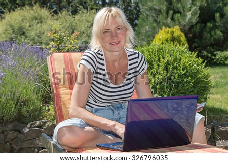 Relaxed blonde middle aged woman is sitting outdoors on the sun lounger with open notebook and is looking to the camera. Garden with blooming lavender is in the background.  - stock photo