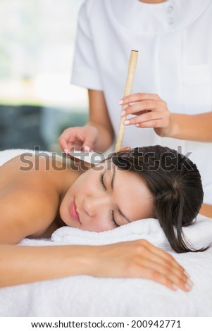 Relaxed brunette getting an ear candling treatment at the spa