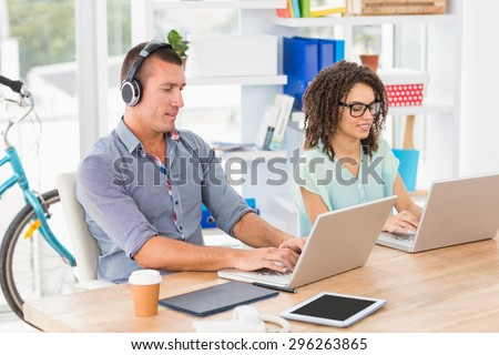 Relaxed business colleagues working on laptop in the office - stock photo