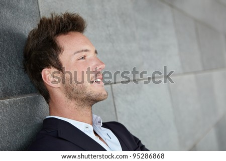 Relaxed business man thinking with head leaning on wall - stock photo