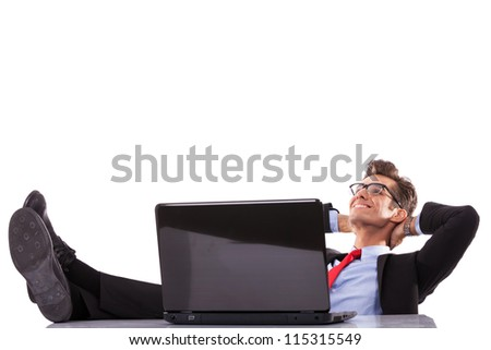 Relaxed business man working with a laptop in his office, dreaming at his success - stock photo