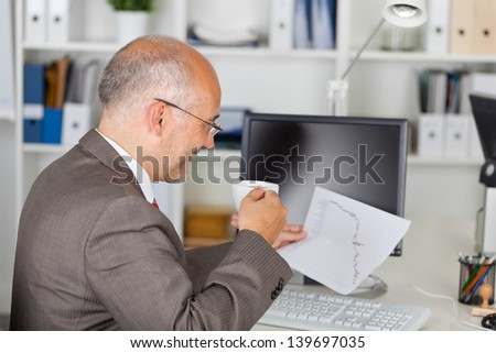 relaxed businessman drinking coffee at desk - stock photo