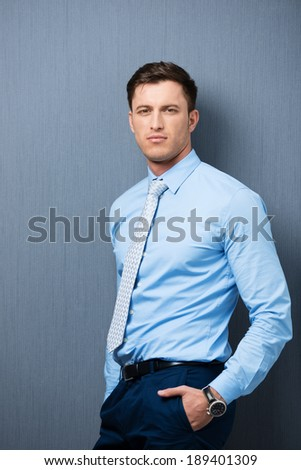 Relaxed businessman eyeing the camera with a speculative thoughtful expression as he leans against a clean blackboard with his hands in his pockets