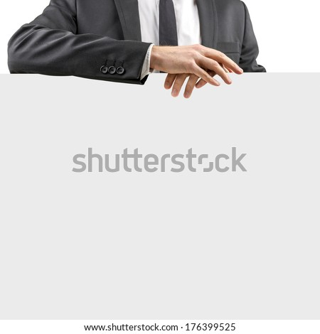 Relaxed businessman in a suit resting his folded hands on a blank white sign with copyspace for your text or advertisement , closeup torso view isolated on white. - stock photo