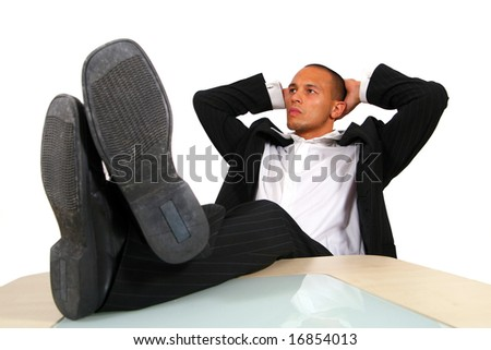 Relaxed Businessman In Office A young satisfied businessman sitting by desk at office feet on table thinking. Isolated over white. - stock photo