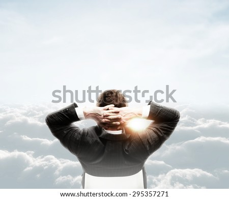 relaxed businessman looking at cloud in sky - stock photo