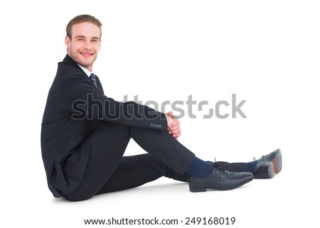 Relaxed businessman sitting and smiling on white background